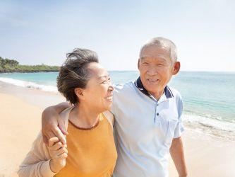 Happy Asian Seniors Walking On Beach